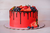 beautiful home made bright red cake with strawberry and blueberry berries, chocolate frosting on white table