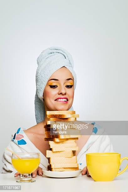 Beautiful hungry woman eating toasts for breakfast.