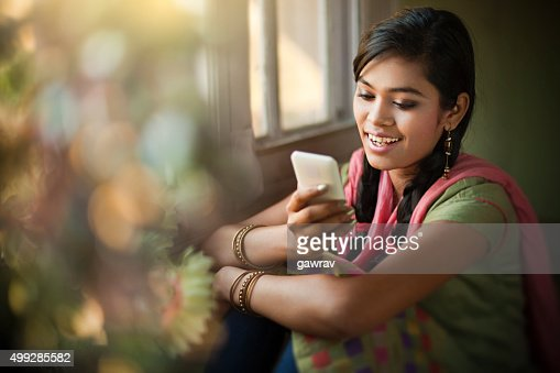 Beautiful Indian girl reading SMS at the time of festival.