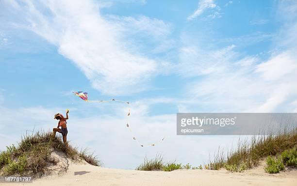 Bella donna indiana arrampicata su una collina per volare il suo aquilone