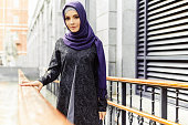 Beautiful Islamic woman in traditional oriental clothes standing on a city street, Russia