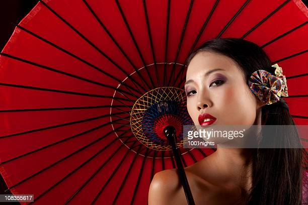Beautiful Japanese geisha with a red umbrella
