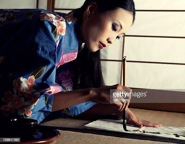 Beautiful Japanese geisha writing a calligraphic type