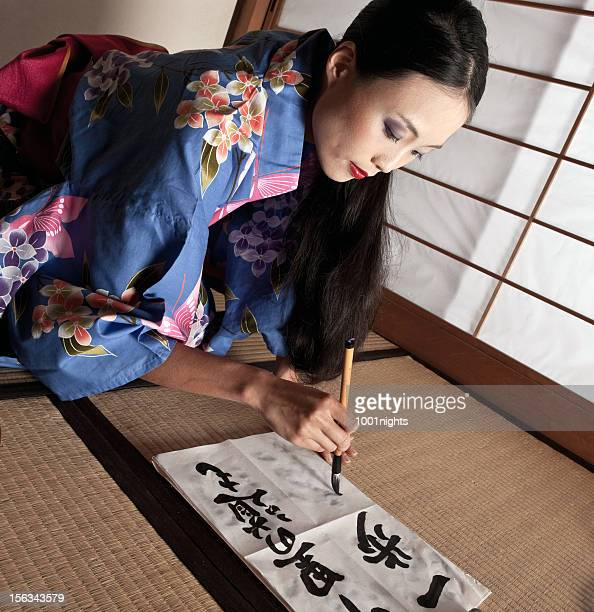 Beautiful Japanese geisha writing a calligraphic type