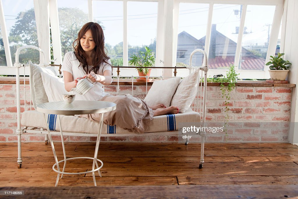 Beautiful Japanese girl drinking tea in a countryhouse : Stock Photo