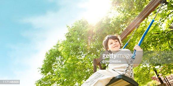 beautiful kid play outdor on swing