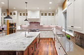 Large kitchen interior with hardwood floors, two sinks, pendant lights, and wrap around cabinets