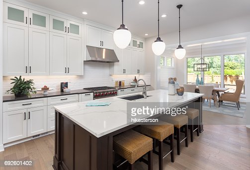 beautiful kitchen in new luxury home with island, pendant lights, and hardwood floors. Includes view of dining room. : Stock Photo