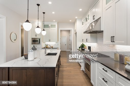 beautiful kitchen in new luxury home with island, pendant lights, and glass fronted cabinets : Stock Photo