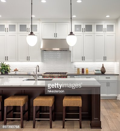beautiful kitchen in new luxury home with island, pendant lights, oven, range, and hardwood floors. : Stock Photo