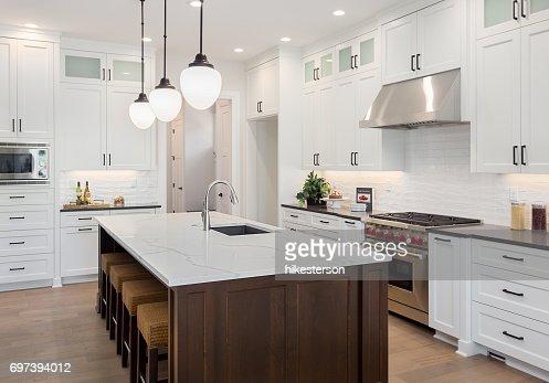 beautiful kitchen in new luxury home with large island, pendant lights, oven, range, and hardwood floors. : Stock Photo