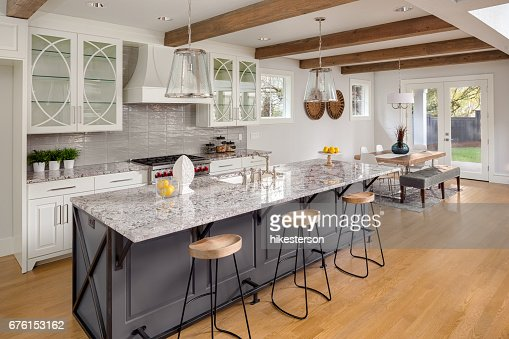 beautiful kitchen with lights off in new luxury home with island, pendant lights, and glass fronted cabinets, and view of dining room : Stock Photo