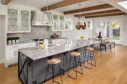 Beautiful Kitchen With Lights Off In New Luxury Home Island Pendant And Glass Fronted Cabinets View Of Dining Room