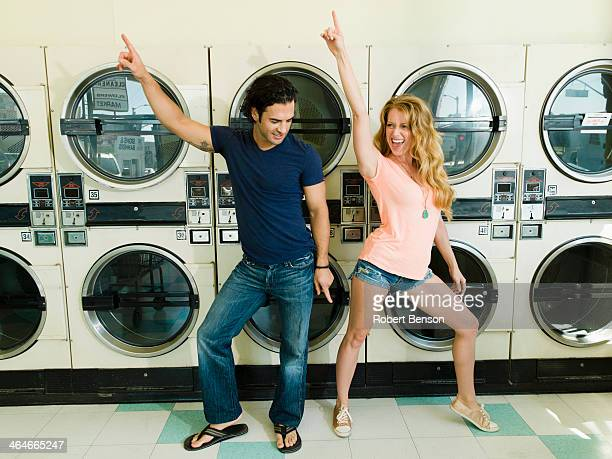 A beautiful lady dances with a smart young man in San Diego coin laundromat.