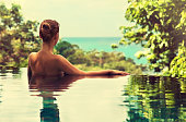 Young girl watching a sea line from the swimming pool. Image of rest, harmony and comfort. Spa treatments.