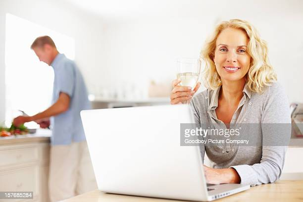 Beautiful lady with wine and laptop while man cutting vegetables