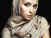 Studio fashion portrait of beautiful lady wrapped in a orient shawl