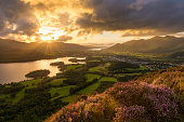 Sun setting behind moody clouds with dramatic evening light in the English Lake District.