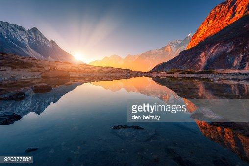 Beautiful landscape with high mountains with illuminated peaks, stones in mountain lake, reflection, blue sky and yellow sunlight in sunrise. Nepal. Amazing scene with Himalayan mountains. Himalayas : Foto de stock