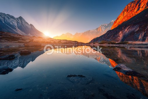 Beautiful landscape with high mountains with illuminated peaks, stones in mountain lake, reflection, blue sky and yellow sunlight in sunrise. Nepal. Amazing scene with Himalayan mountains. Himalayas : Stock Photo