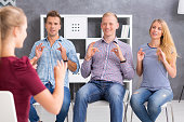 Group of young people learning a sign language