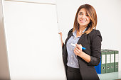 Portrait of a gorgeous Hispanic woman teaching Spanish and standing next to a flip chart