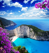 Navagio beach, famous lanscape of Zakinthos island, Greece with bouganvilea flowers