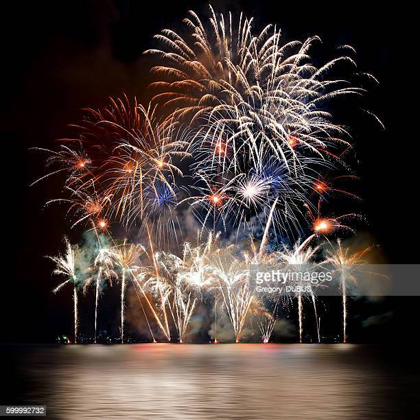 Beautiful large colorful fireworks display with illuminated water reflections