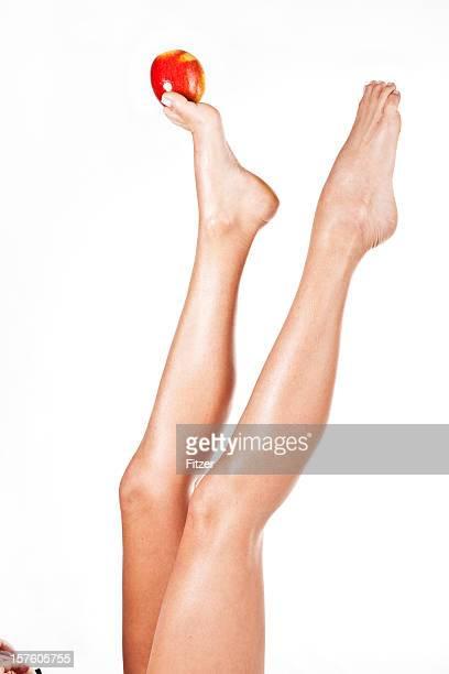 Belles jambes équilibre une pomme fond blanc