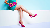 Perfect skin long legs woman with violet pink color pumps heels shoes and clutch bag.