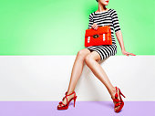 Woman wearing stripe dress, red elegant sandals heels, holding an orange purse bag sitting with the colourful green background.