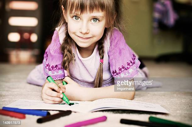 Beautiful little girl and her coloring book.