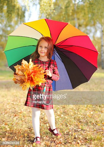 Beautiful little girl child and colorful umbrella in autumn day : Stock Photo