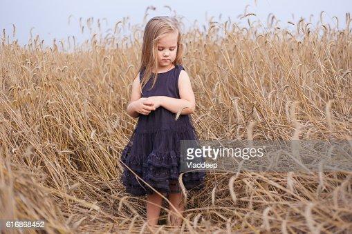Beautiful little girl in ripe rye field staying in black : Stock Photo