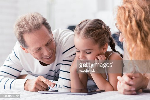 Beautiful little girl looking at the tablet with her grandparents : Stock Photo