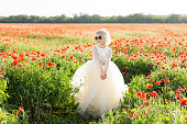 beautiful little girl in a field of poppies, childhood, happiness, fashion, children, nature and summer flowers concept - smiling girlie in white fancy dress posing on poppy field, with sunglasses