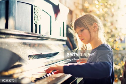 Beautiful little girl playing on grandmother piano