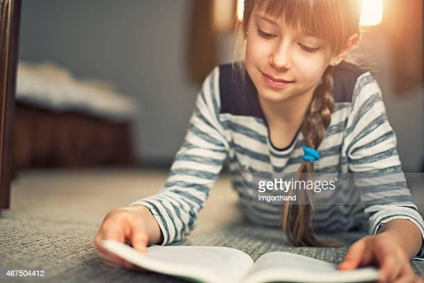 Bela Menina ler um livro sobre o tapete.