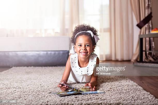Schönes kleines Mädchen liest ein Buch auf dem Teppich.