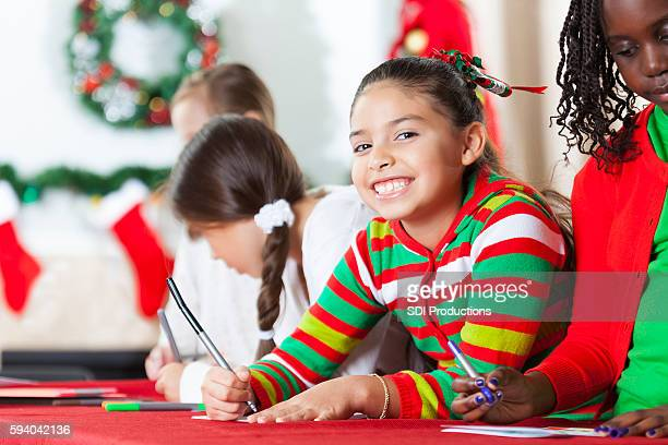 Beautiful little girl smiles confidently whilte writing a Christmas card