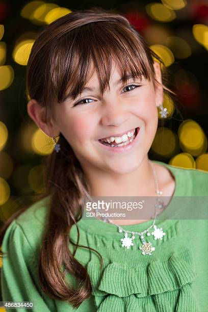 Beautiful little girl smiling in front of decorated Christmas tree