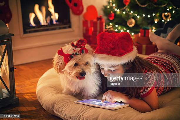 Beautiful little girl using digital tablet on Christmas night