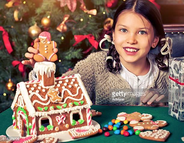 Hermosa niña con una casa de galleta de jengibre