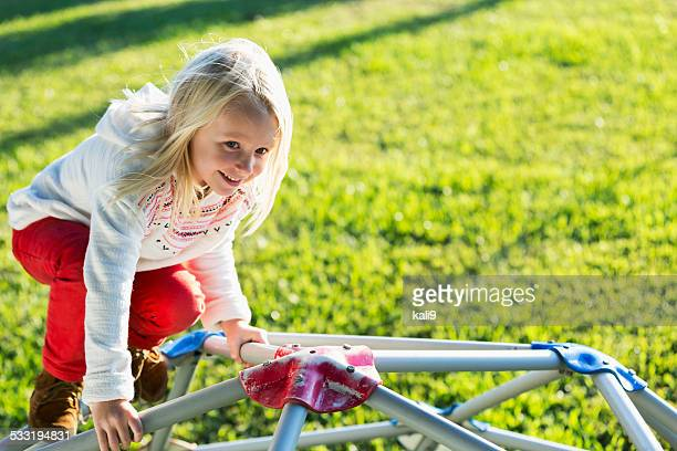 Beautiful little girl with blond hair on playground