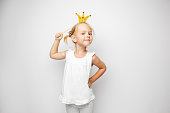 Beautiful little girl with paper crown posing on white background at home