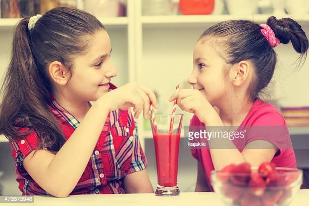 Belle petite fille boire un cocktail à la fraise