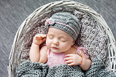 Beautiful little newborn girl 1 month sleeps in a wattled basket. Clousup picture