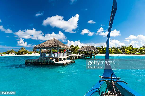 Beautiful Maldives beach with jetty and dhoni and a seaplane