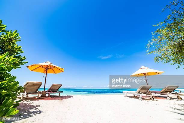 Beautiful Maldives beach with sunbeds and blue sky