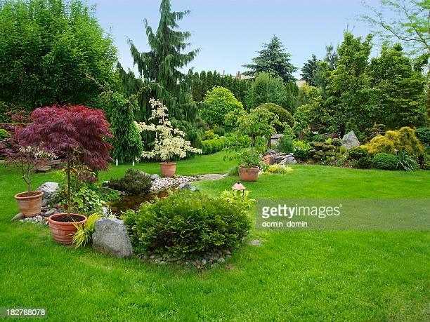Wunderschön gepflegten Garten mit Büschen und Bäumen, Steine, Teich, saftige Gras